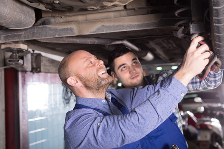 mounting holes: Two smiling professional car mechanics checking up pressure in tires at workshop