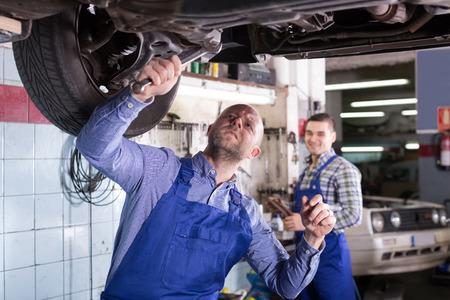 happy mechanics fixing car tire leak