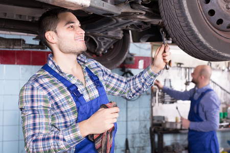 serviceman: Professional positive serviceman  repairing car of client Stock Photo
