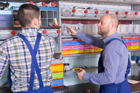 storing: Two workmen standing near storage shelves in auto repair shop Stock Photo