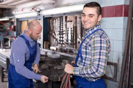 journeyman: Two smiling workmen in repairshop