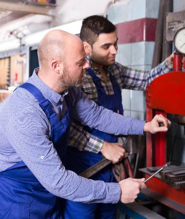 repairmen: Two repairmen in a workshop using tools