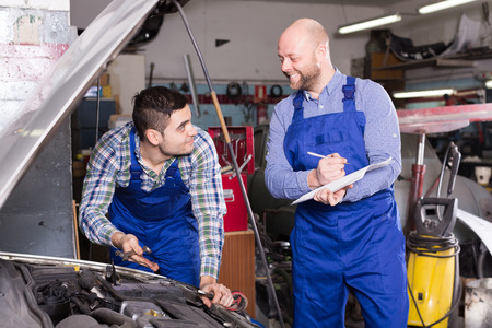 motor mechanic: Workman calculating the price of work at the auto repair shop Stock Photo