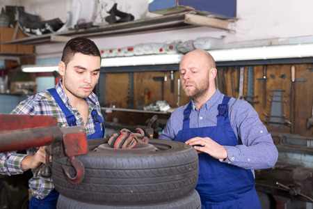 specialists: Cheerful adult mounting specialists in coveralls working at auto repair shop. Focus on the right man Stock Photo