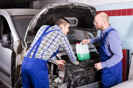 specialists: Happy mounting specialists in coveralls working at auto repair shop Stock Photo