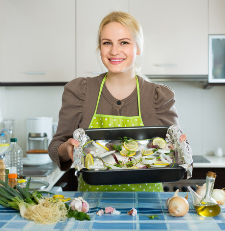 cook griddle: Happy smiling housewife cooking fish at home kitchen