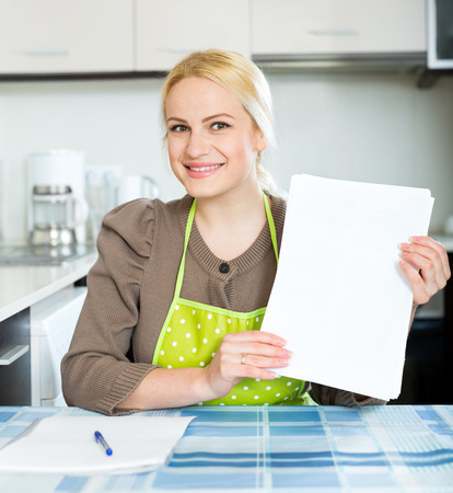 parsimony: Young blonde woman with paper at home kitchen