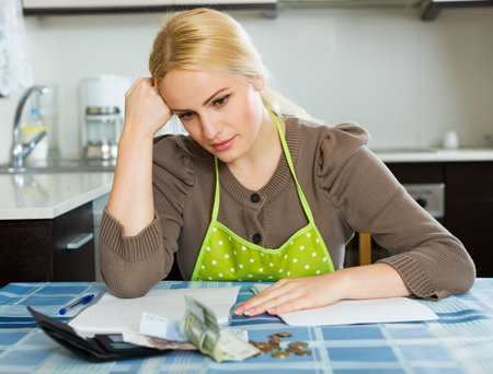 penury: Serious woman calculating the family budget at  home