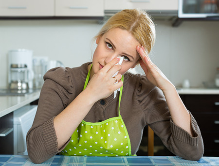 aloneness: Unhappy lonely blonde girl sitting sad in kitchen at home Stock Photo