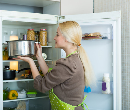fridge: Blonde girl looking for something in fridge at home kitchen