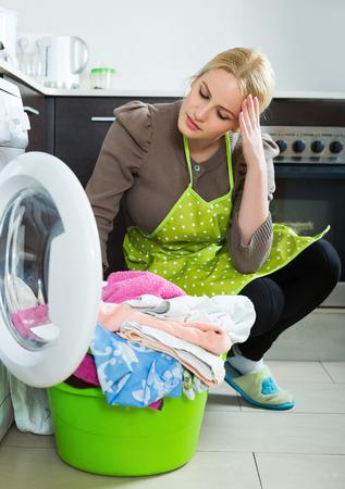 lavander: Mujer rubia Cansado haciendo lavandería con lavadora en la cocina en casa Foto de archivo