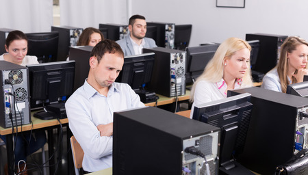 harassing: Bored american staff sitting at desks and looking at PC screens Stock Photo