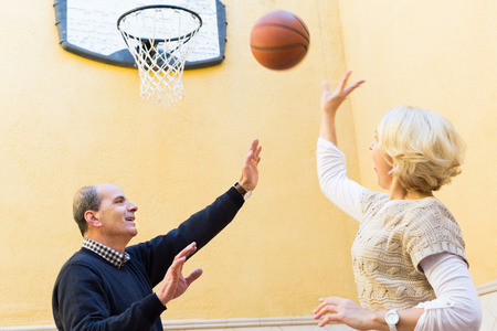 Happy smiling senior family couple playing basketball in patio photo