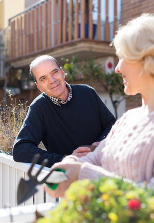 horticultural: Positive elderly woman with horticultural sundry and aged man drinking tea in patio