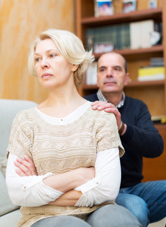 flatter: Guilty mature husband asking wife for forgiveness Stock Photo