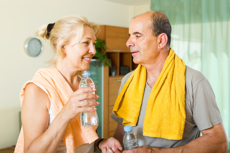 spouses: Smiling elderly spouses with bottles of water after morning exercises