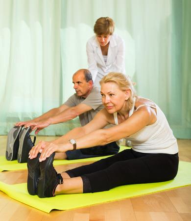 personal medico: El personal m�dico en el gimnasio de ayudar a los c�nyuges de alto nivel para tomar posici�n correcta Foto de archivo