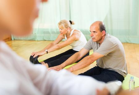 remedial: Doctor keeping eye at senior couple during training at gym. Focus on man