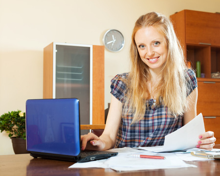 parsimony: smiling long-haired woman working with financial documents and laptop at home interior Stock Photo