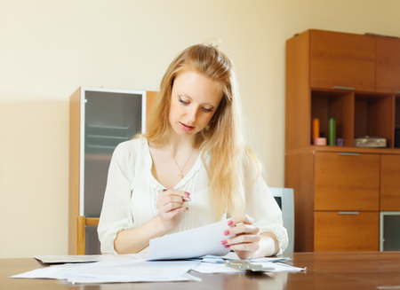 parsimony: serious blonde woman staring financial documents at table in home interior Stock Photo