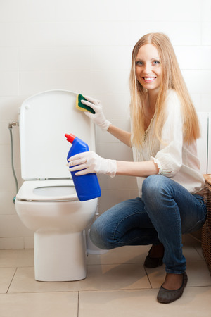 Smiling long-haired housewife cleaning toilet bowl photo