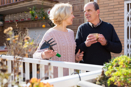balcon: Elderly woman talking with smiling male neighbor at balcon