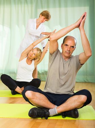 personal medico: El personal m�dico que ayudan a pareja de ancianos a tomar posici�n correcta en el gimnasio