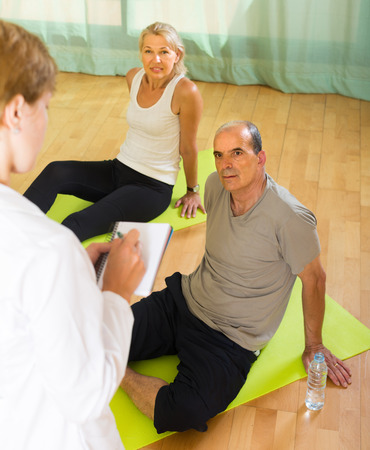studio happy overall: Doctor keeping eye at senior couple during training. Focus on man Stock Photo