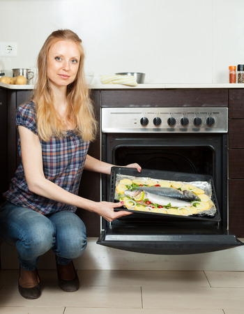 ordinary: Ordinary woman cooking fish in oven at home kitchen Stock Photo