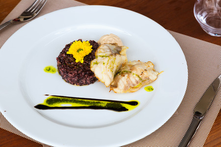 recipe decorated: Pollock with black rice and sauce on  plate at restaurant table