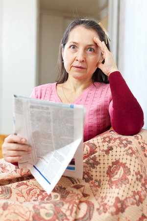wonderment: wonder and affliction mature woman with newspaper at home