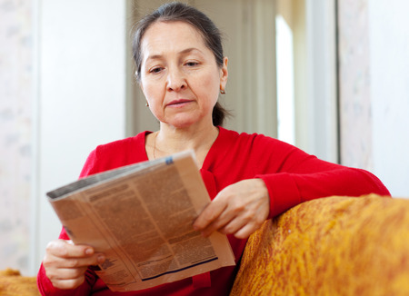 thoughtful woman: serious mature woman looks newspaper at home