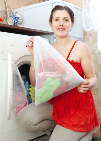 woman  in red  loading the washing machine with laundry bag photo