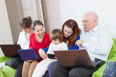 muchas personas: La familia feliz disfruta en el sofá en sala de estar con unos ordenadores portátiles en el hogar