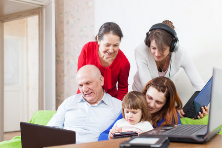 family uses few various electronic devices in home photo