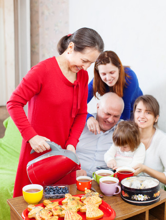 gladful: Mature woman pours tea from teapot for her family at home Stock Photo