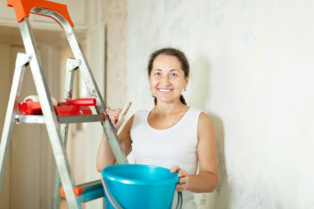 priming brush: Mature woman makes repairs at home