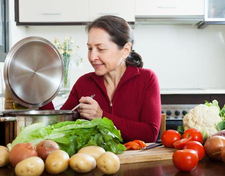 Positieve rijpe vrouw koken met pollepel in binnenlandse keuken Stockfoto