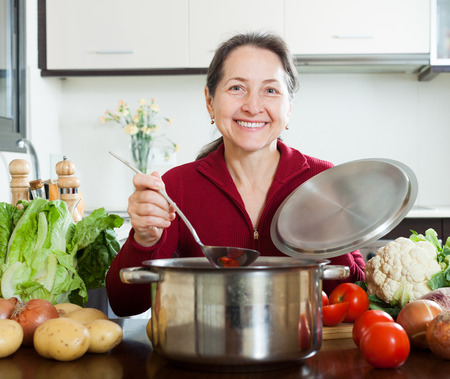 lent: Happy mature woman cooking lent diet soup in  kitchen