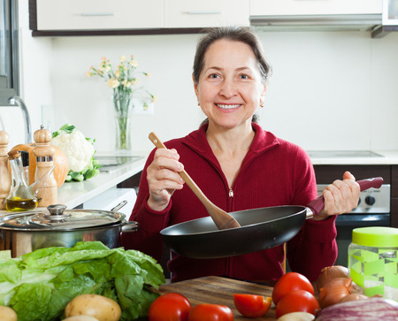 fryingpan: Portrait of happy mature housewife with frying-pan in home kitchen