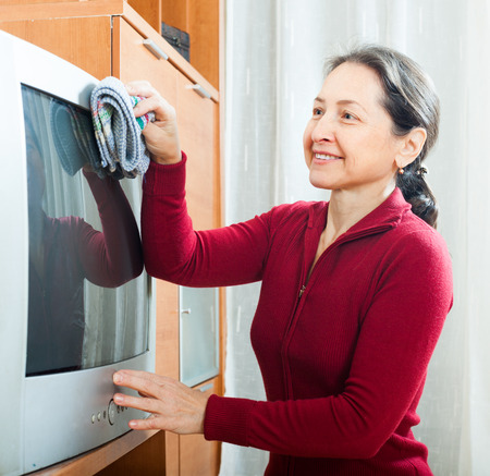 dusting: Smiling mature woman dusting TV at home Stock Photo