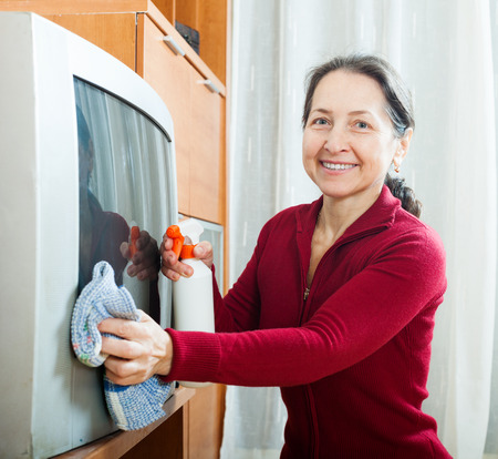 Smiling mature woman wiping the dust  on TV photo