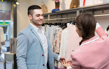 Happy young girl with boyfriend choosing new apparel in clothing store photo