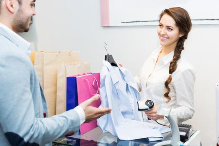 store clerk: Beauty store clerk serving purchaser at cash register desk