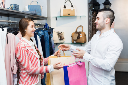 purchaser: Young store clerk serving happy purchaser at fashionable apparel store