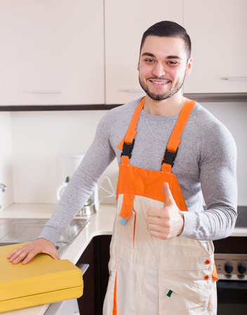 aftersales: Portrait of handsome skilled workman at residential kitchen