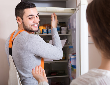 aftersales: Workman visiting female for after-sales service of refrigerator Stock Photo
