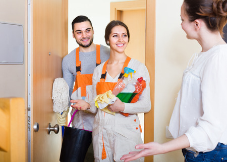 Cheerful woman greeting cleaning service team holding cleansers. Focus on girl