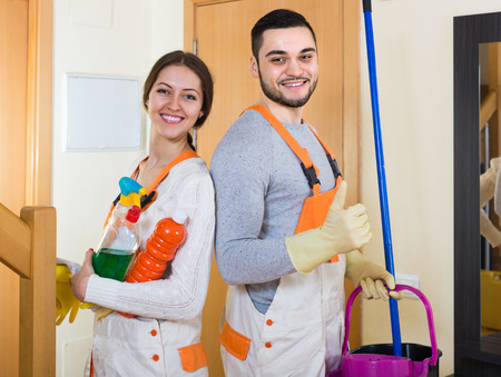 houseman: Portrait of professional cleaners with equipment at the doors of client house