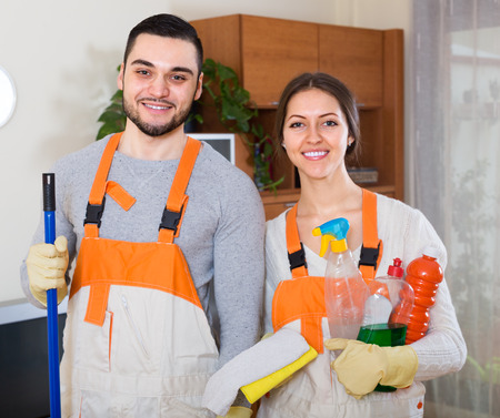 company premises: Professional smiling  cleaners cleaning in room